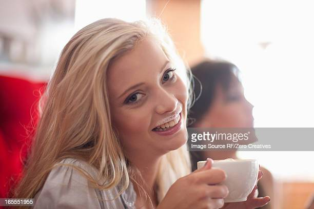 Woman with milk mustache in cafe