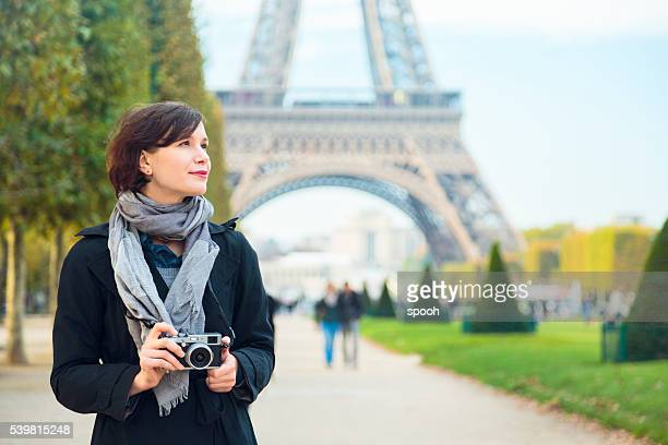 Woman with mirrorless camera in front of Eiffel tower, Paris