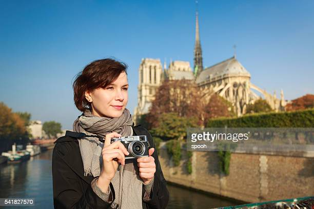 Woman with mirrorless camera in front of Notre Dame, Paris.