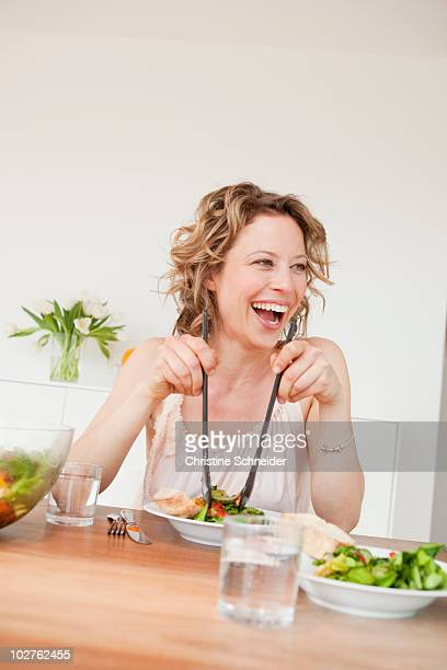 Woman with mixed salad on table
