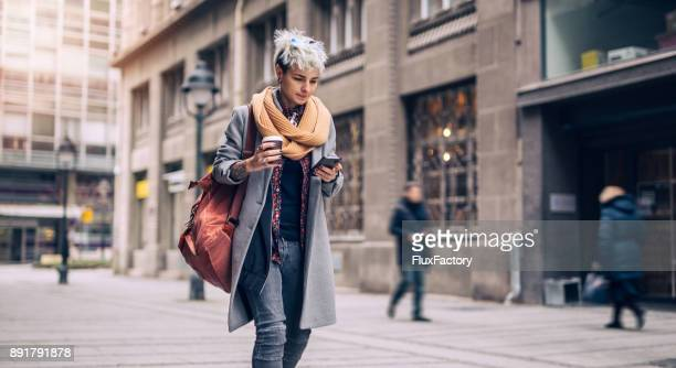 woman with mobile and coffee on the street - gender bender foto e immagini stock