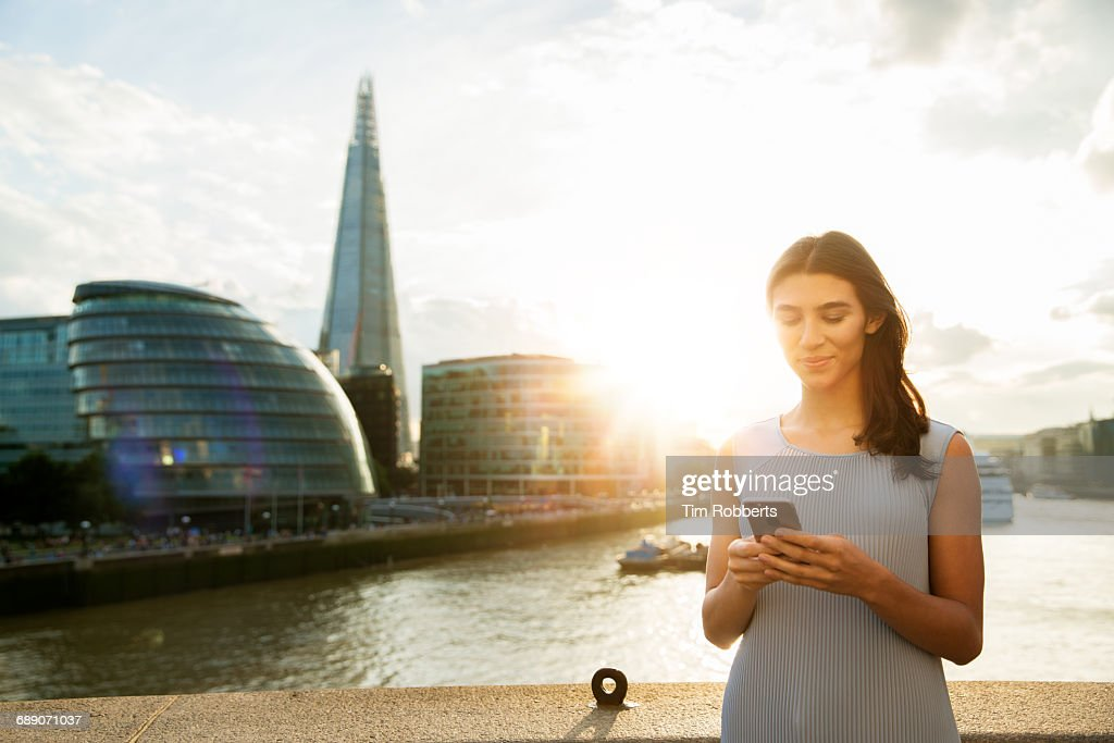 Woman with mobile at sunset : Stock Photo