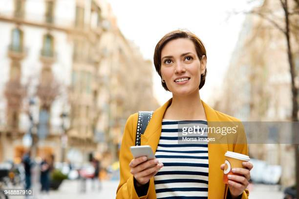 woman with mobile phone and disposable cup in city - yellow coat stock pictures, royalty-free photos & images