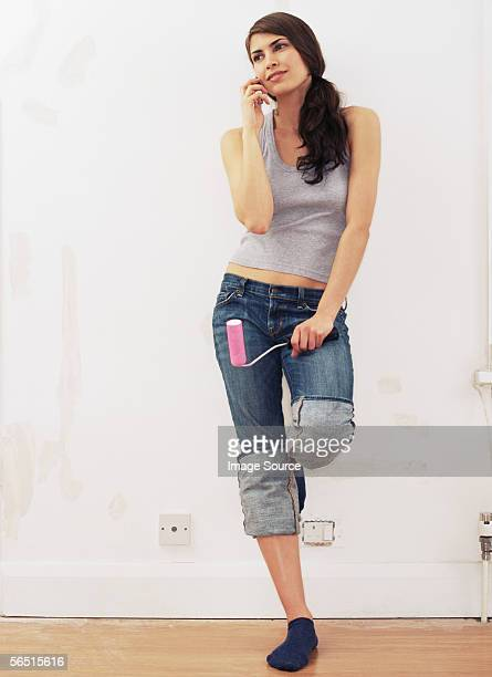 Woman with mobile phone and paint roller