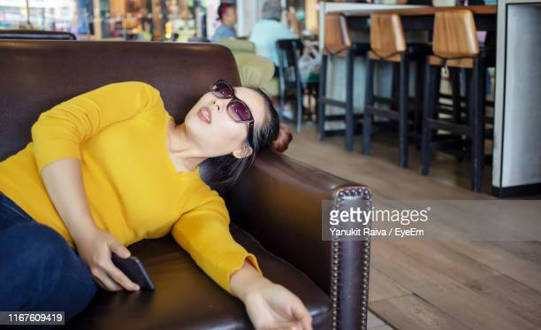 woman with mobile phone fainted on sofa in cafe - fainting stock pictures, royalty-free photos & images