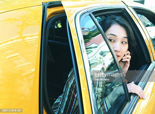 Woman with mobile phone looking out of taxi cab window