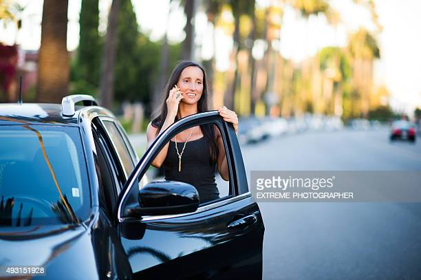 Woman with mobile phone next to black SUV