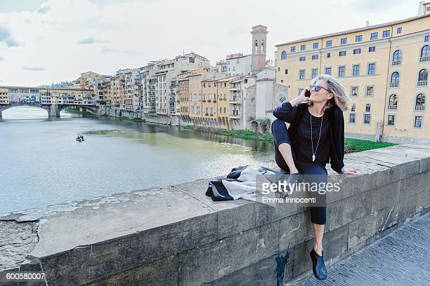 woman with mobile phone on Arno river bank