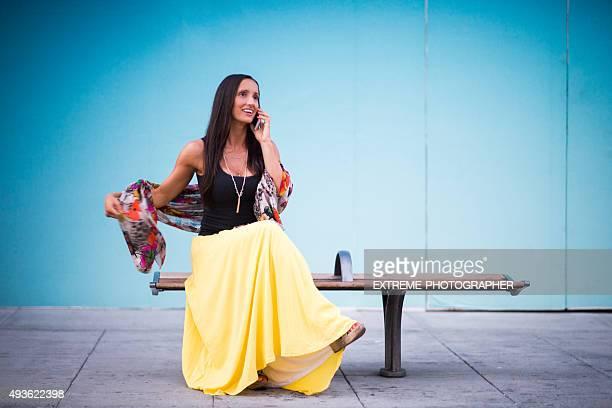 Mujer con teléfono móvil sentado en el banco