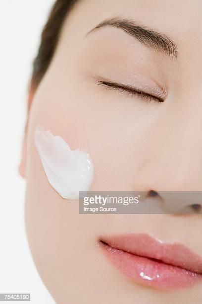 Femme avec hydratant sur sa joue