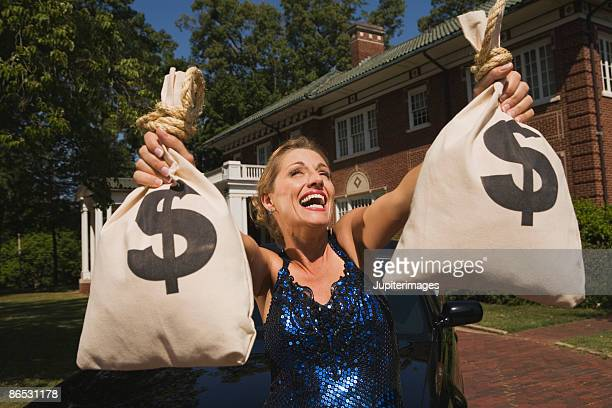 Woman with money bags in front of mansion
