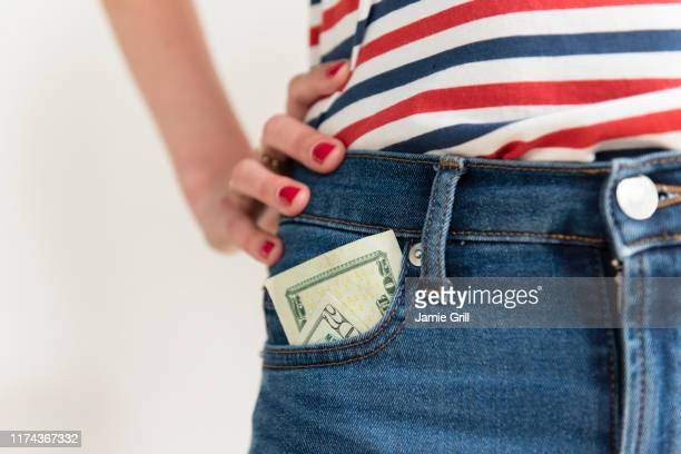 woman with money in her jeans pocket - pocket stock pictures, royalty-free photos & images