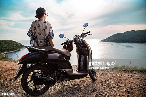 Woman with motorbike watching the sunset