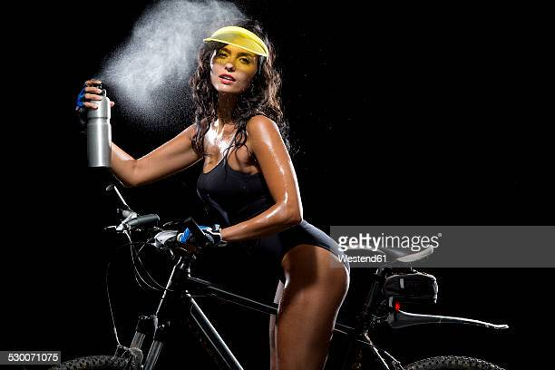woman with mountain bike refreshing herself with water - bend over cleavage stock photos and pictures