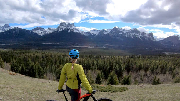 Woman with mountain e-bike pauses on high alpine pass and looks out over valley