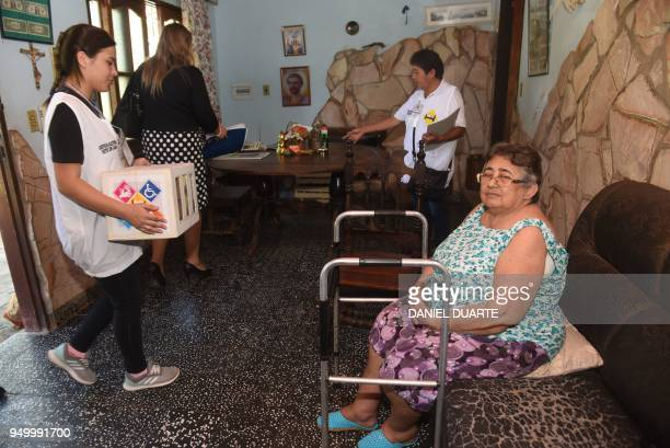A woman with moving difficulties receives election staffers to vote at her house during presidential elections in Asuncion on April 22 2018 Opinion...