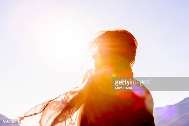 woman with moving hair and scarf in sunlight in a windy day - zonlicht stockfoto's en -beelden