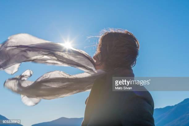 woman with moving hair and scarf in sunlight in a windy day - overcoat stock pictures, royalty-free photos & images