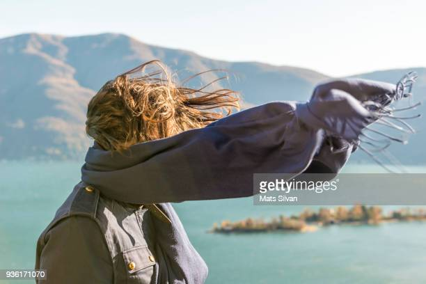 woman with moving hair and scarf in sunlight in a windy day - wind stockfoto's en -beelden