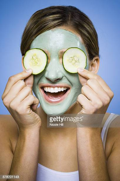 Woman with mud mask and cucumber slices smiling