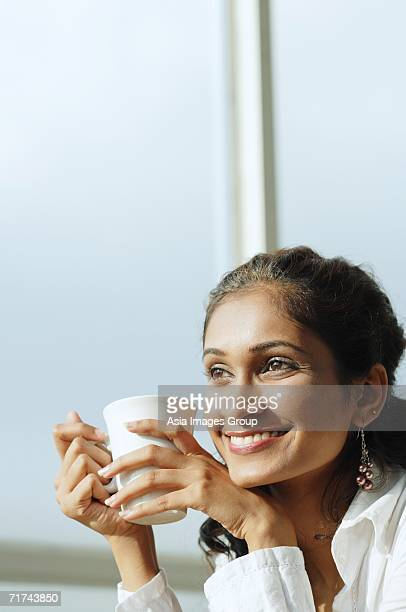 Woman with mug in hand, smiling, looking away