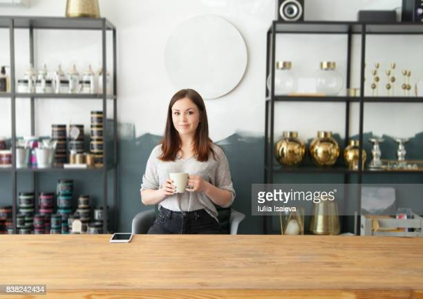 Woman with mug in shop behind counter
