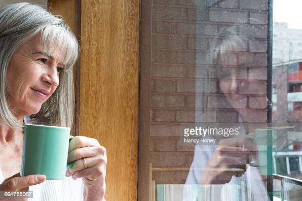 Woman with mug, looking through window