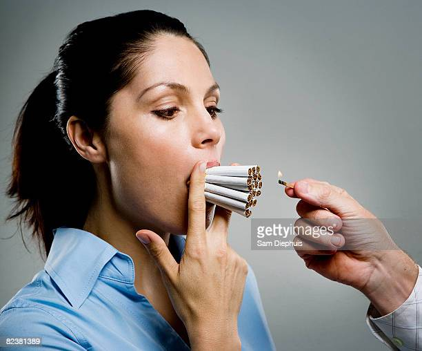 Woman with multiple cigarettes in mouth, man holding match