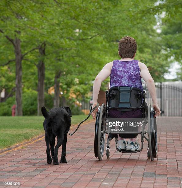 Woman with Multiple Sclerosis in a park with a service dog