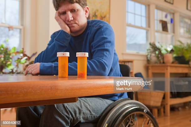 Woman with multiple sclerosis in a wheelchair choosing between perscription medicines