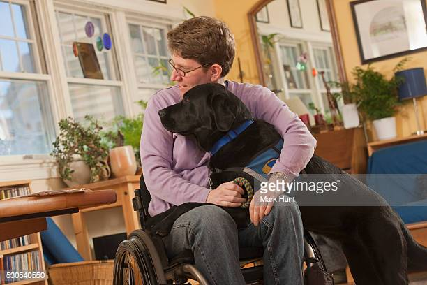 Woman with multiple sclerosis in a wheelchair hugging her service dog