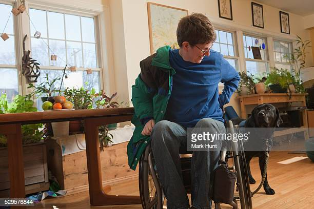 woman with multiple sclerosis in a wheelchair putting on her coat with service dog watching her - multiple sclerosis stock photos and pictures