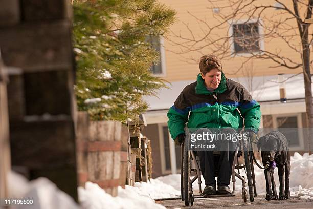 woman with multiple sclerosis in a wheelchair with a service dog in winter - multiple sclerosis stock photos and pictures