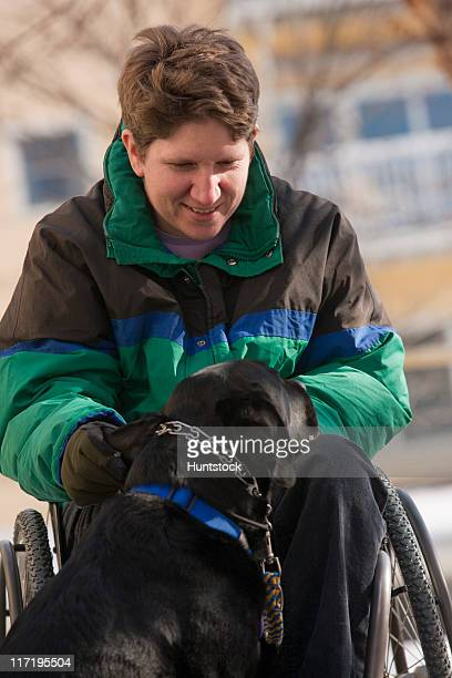 Woman with multiple sclerosis playing with a service dog in winter