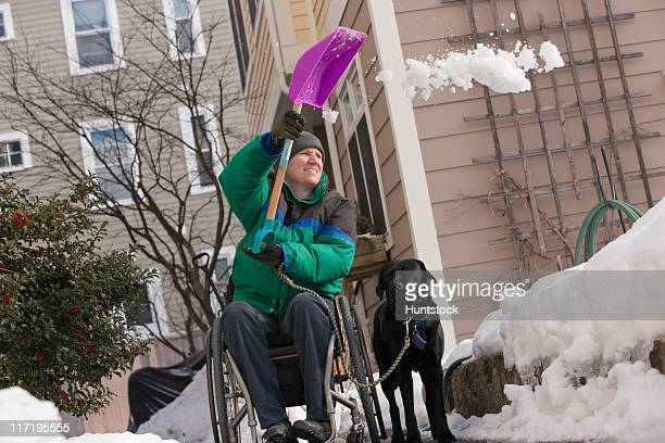 woman with multiple sclerosis shoveling snow in a wheelchair with a service dog - multiple sclerosis stock photos and pictures