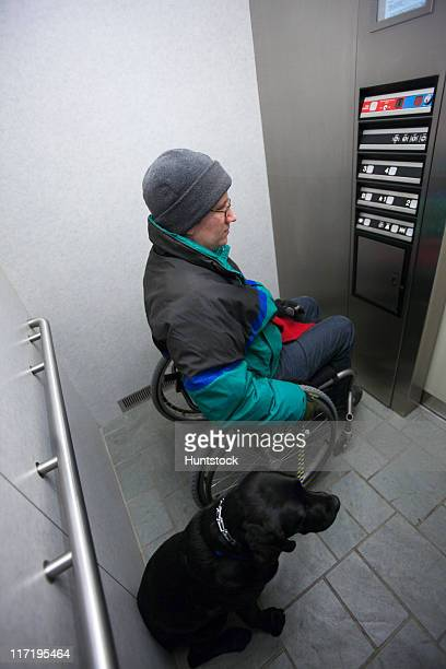 Woman with multiple sclerosis using an elevator with a service dog