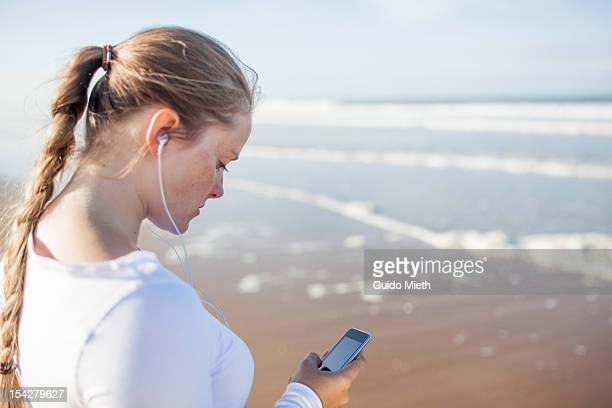 Woman with music player seaside.