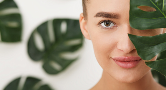 Woman with natural make up and green leaf 1134260957