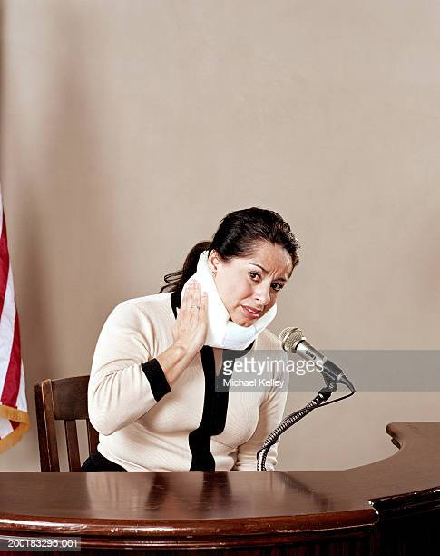 woman with neck brace testifying in court - 法的手続 ストックフォトと画像