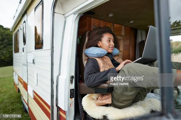 woman with neck pillow using laptop in motor van - lifestyle stock pictures, royalty-free photos & images