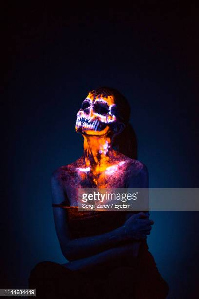 woman with neon face paint against black background - body paint stock pictures, royalty-free photos & images