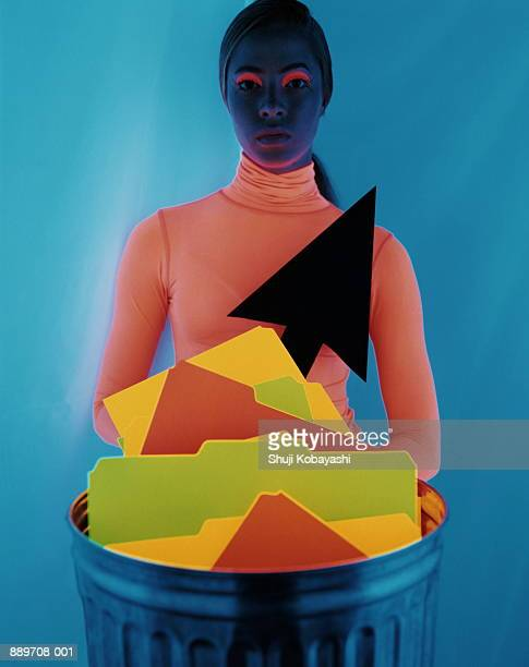 Woman with neon make-up, behind dustbin with folders and arrow