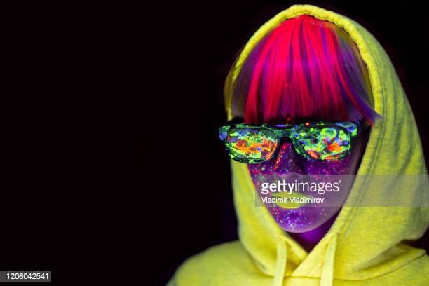 mulher com pó de maquiagem neon no rosto e roupas, óculos de sol coloridos - cor saturada - fotografias e filmes do acervo
