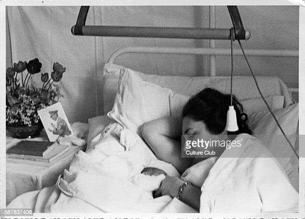 A woman with newborn baby lies in her hospital bed with a portrait of Hitler at bedside