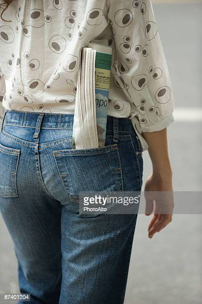 Woman with newspaper rolled up in back pocket of jeans, cropped view