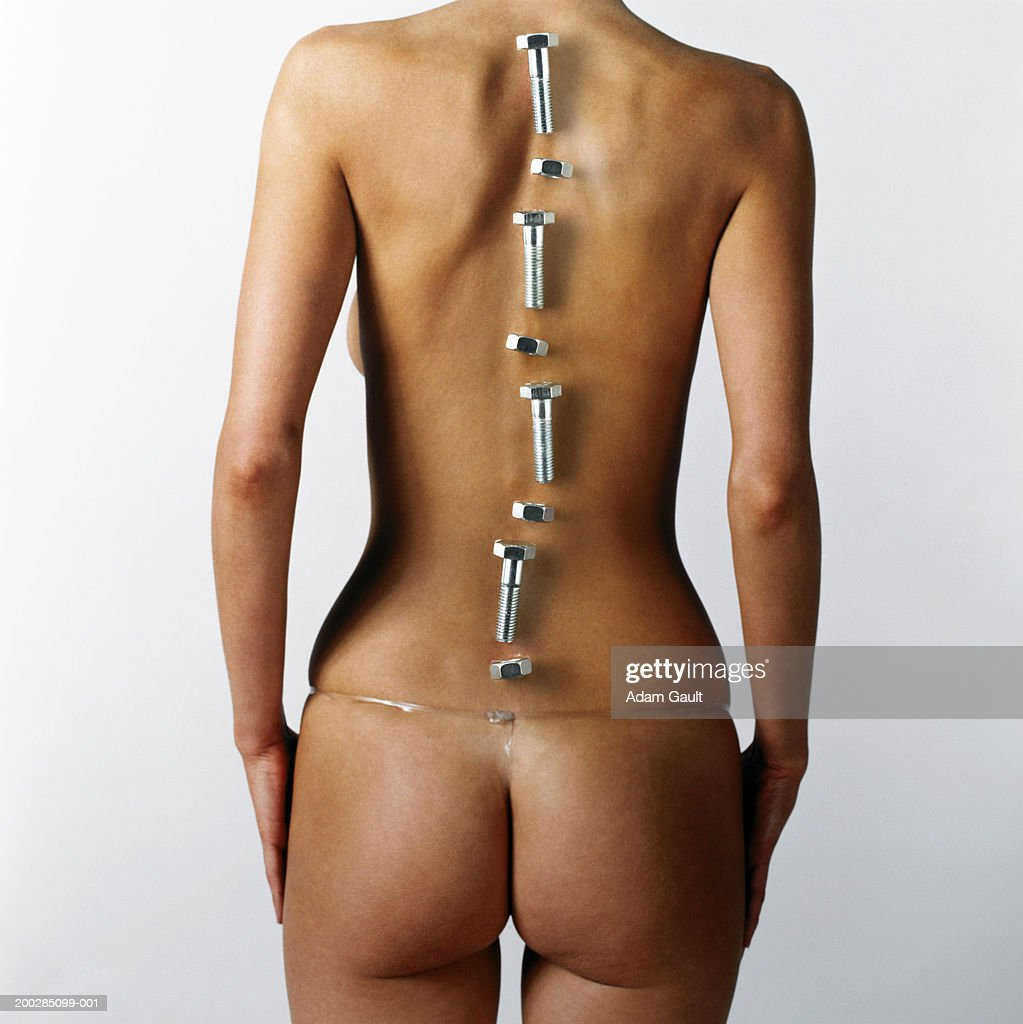 Woman with nuts and bolts placed over line of backbone, rear view : Stock Photo