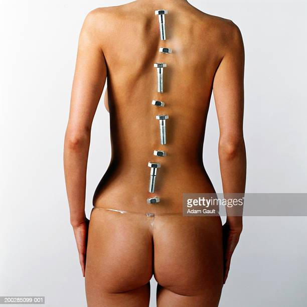 woman with nuts and bolts placed over line of backbone, rear view - backache stock pictures, royalty-free photos & images