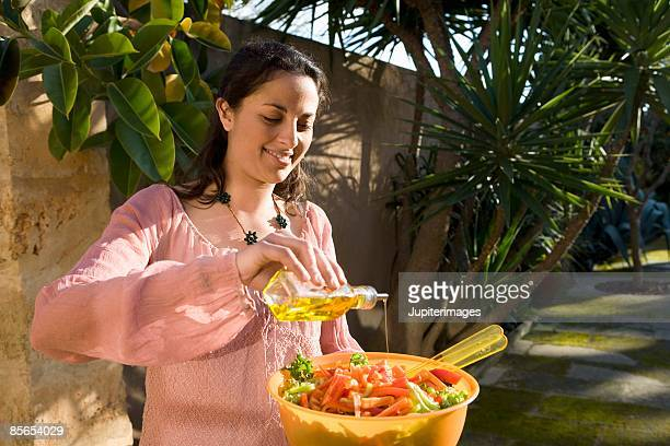 Woman with olive oil and salad