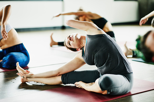 Woman with one arm in seated side bend pose during hot yoga class - gettyimageskorea