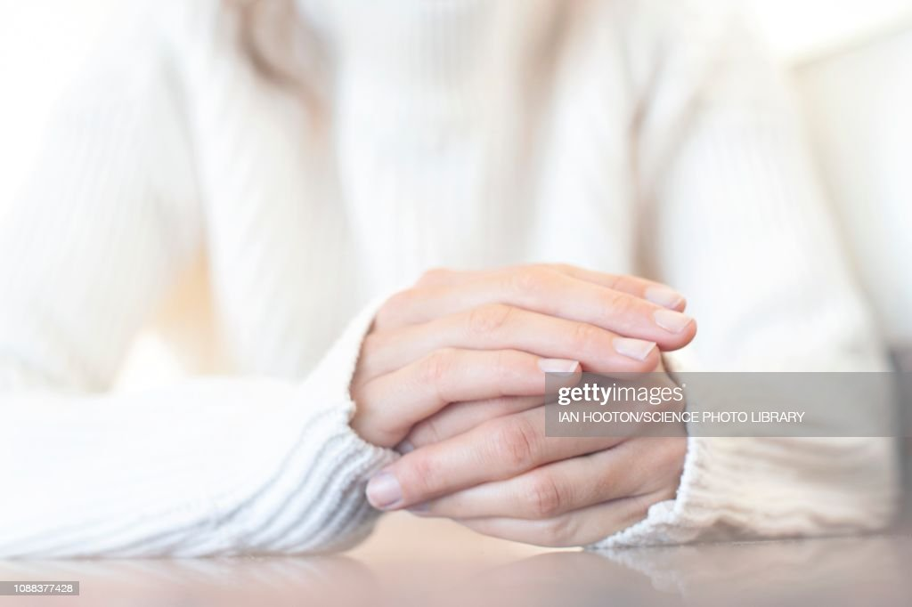 Woman with one hand on top of the other : Stock Photo